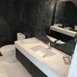 black stone bathroom with solid surface counters