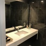 black stone bathroom with white counters