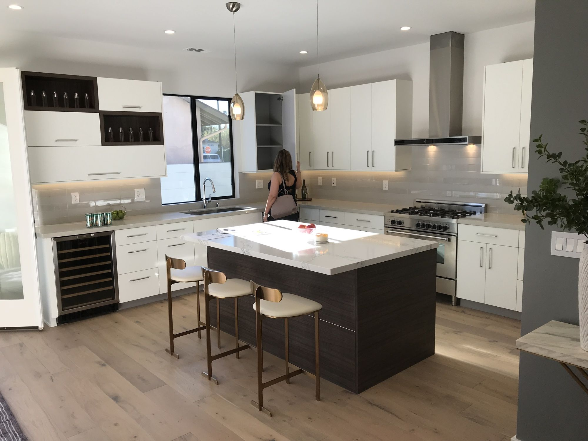 woman in Los Angeles opening up her new ktichen cabinet doors