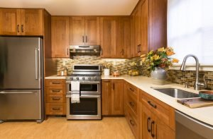 Contemporary upscale home kitchen interior with cherry wood cabinets, quartz countertops, linoleum floors & stainless steel appliances including refrigerator & gas stove